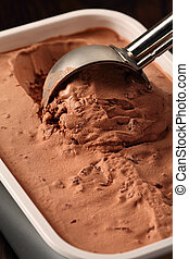 Photo of a metal scoop digging into a tub of chocolate ice cream.