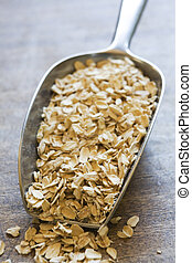 Scoop of oats on wooden counter