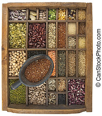 rustic scoop of red quinoa and a variety of beans, lentils, grain, seeds in old wooden typesetter case, isolated with clipping path, wide angle view showing box interior