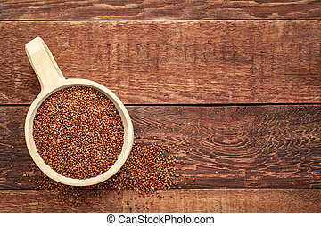 scoop of red quinoa grain