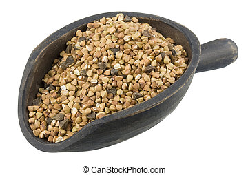 roasted buckwheat on a primitive, dark painted, wooden scoop, isolated on white, clipping path included