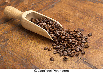 scoop with coffee beans on wooden table
