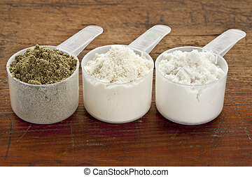 plastic measuring sccops of three protein powders (from left hemp seed, whey concentrate, whey isolate) on a grunge wood surface