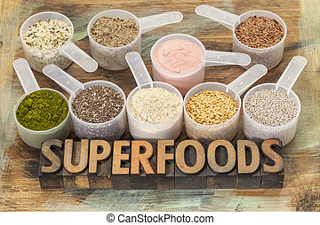 superfoods word in letterpress wood type with plastic scoops of healthy seeds and powders (chia, flax, hemp, pomegranate fruit powder, wheatgrass, maca root)