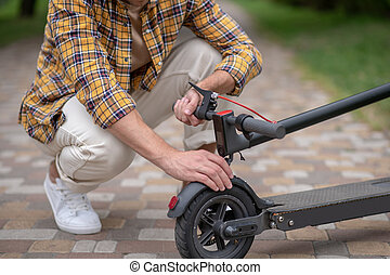Man sitting on his hunkers and fixing his scooter