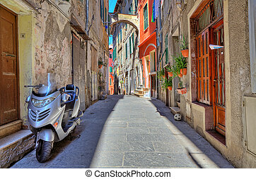 Scooter on narrow street in Ventimiglia, Italy.