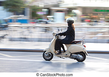 Woman on scooter with motion blur
