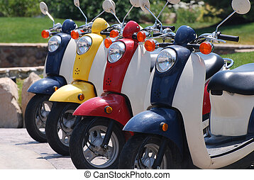 Scooters - Red, Blue and yellow scooters parked in a row.