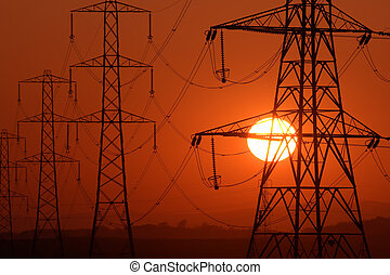 Setting Sun seen through a row of electricity pylons