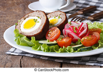 Scotch eggs with salad of fresh vegetables on a plate. ...