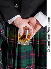 Scotch whiskey - Scotsman holding his glass of whisky behind...