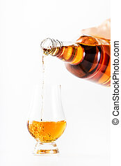 Scotch Whiskey without ice in glass pouring out of the bottle, white background, copy space