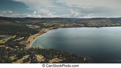Scotland's ocean, Brodick bay aerial view: ferry, ships, boats. Majestic gulf seascape of pier at Firth-of-Clyde Gulf. Nature landscape of wide forests, parks and meadows. Footage shot in 4k, UHD