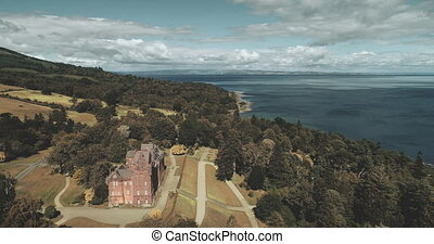 Scottish ocean, Brodick Castle aerial view with magnificent landscape at Atlantic coastline. Trees, park and garden at historical landmark on shore of Firth-of-Clyde. Footage zooming shot n 4K, UHD