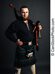 Scottish piper - Young man with beard in scottish costume ...