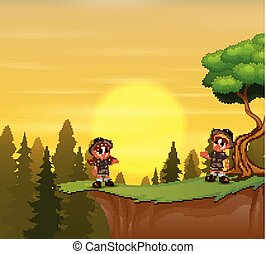 Scout boy and girl standing on mountain cliff of sunset background