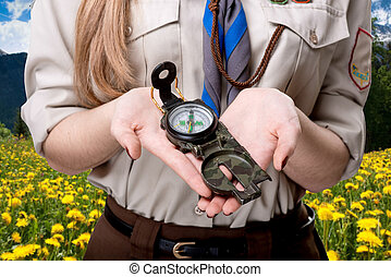 Scout tour - Girl scout holding the compass traveling in the...