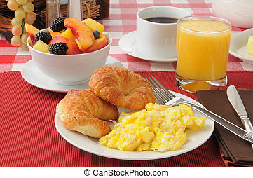 Scrambled eggs and croissants with a fruit salad