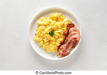 Scrambled eggs and fried bacon on plate