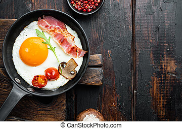 Scrambled eggs in frying pan with pork lard, bread and green feathers in cast iron frying pan, on old dark wooden table background, top view flat lay , with space for text copyspace