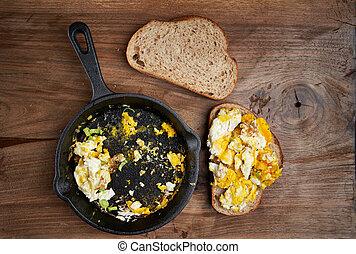 Scrambled eggs on a wooden board