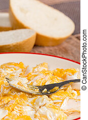 Scrambled eggs on the plate with fork and bread