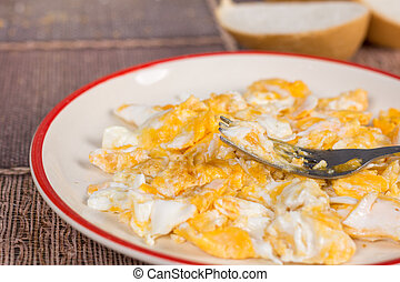 Scrambled eggs on the plate with fork