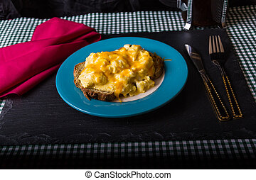 Scrambled eggs topped by grated cheese with red napkin