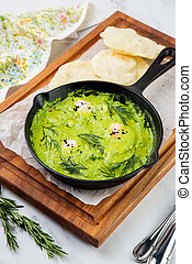 scrambled eggs with herbs, dill, celery and broccoli in a skillet with lean crispbread