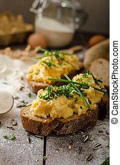 Scrambled eggs with herbs on wheat-rye crispy bread, homemade