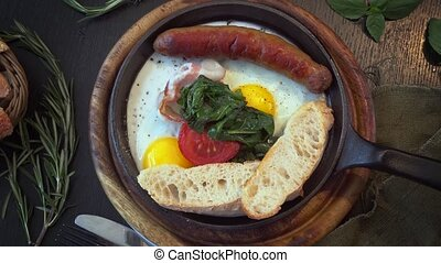 scrambled eggs with sausage and spinach in a skillet in the...