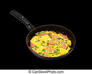 scrambled eggs with sausage in a skillet over a black background