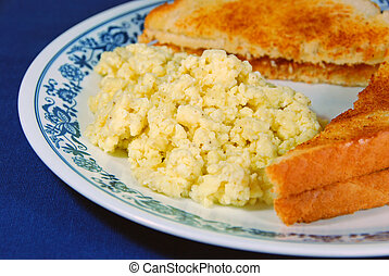 Scrambled Eggs with toast on a blue tablecloth