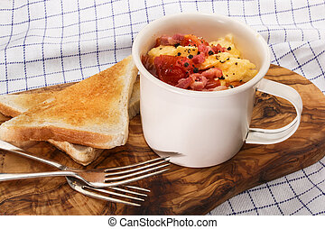 scrambled eggs with tomatoes and fried bacon in a cup