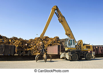 Scrap Heap Crane - A crane with a huge claw in front of a...