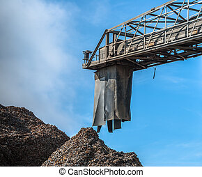 Scrap Metal Processing - A conveyer machine with dumped...