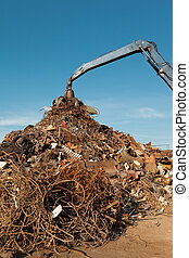 scrap metal recycling center - crane holding rusty metal in...