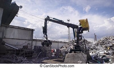 Scrap yard with crane and cars crushed into small cubes -...