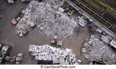 Scrap yard with piles of old metal, car parts and plastic ready for recycling outdoor.