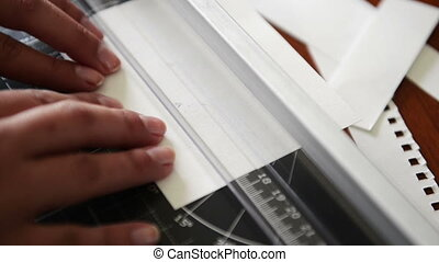 Person cutting paper on a guillotine to trim off paper edges for scrapbooking