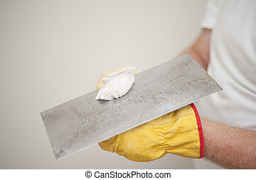 Closeup of scraper and cement filling for house interior renovation construction in hands of handyman and worker, with blurred background and copy space.