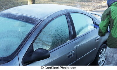 Scraping frosted car windows. - Man scraping the frost off...
