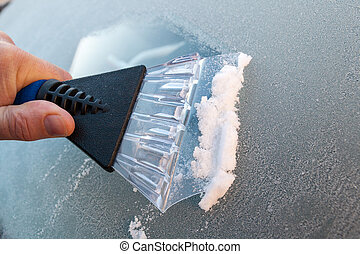 scraping ice from the windshield