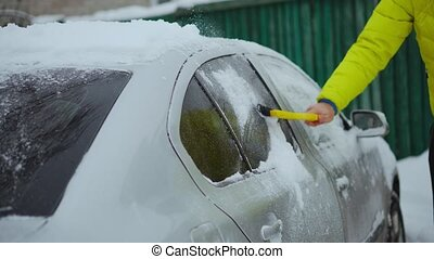 Scraping snow and ice from car windshield. Windshield wipers raised the night before to prevent them getting frozen. Winter driving