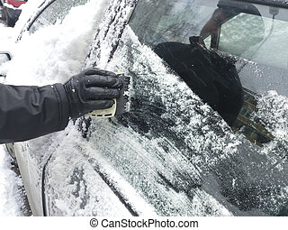 scraping snow and ice from the car windscreen