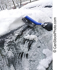 scraping snow and ice from the car