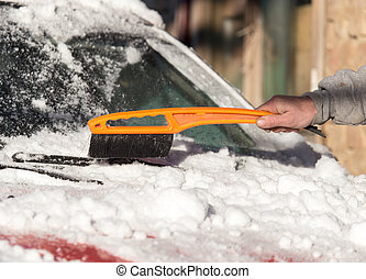 scraping snow from car winter