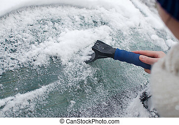 Scraping snow from the car window