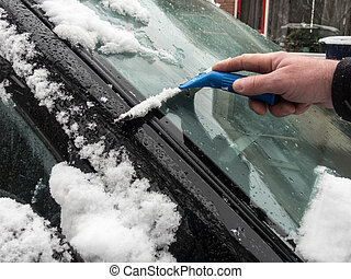 scraping snow from windscreen