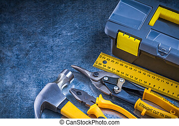 Scratched metallic background with toolbox hammer ruler pliers and tin snips construction concept.